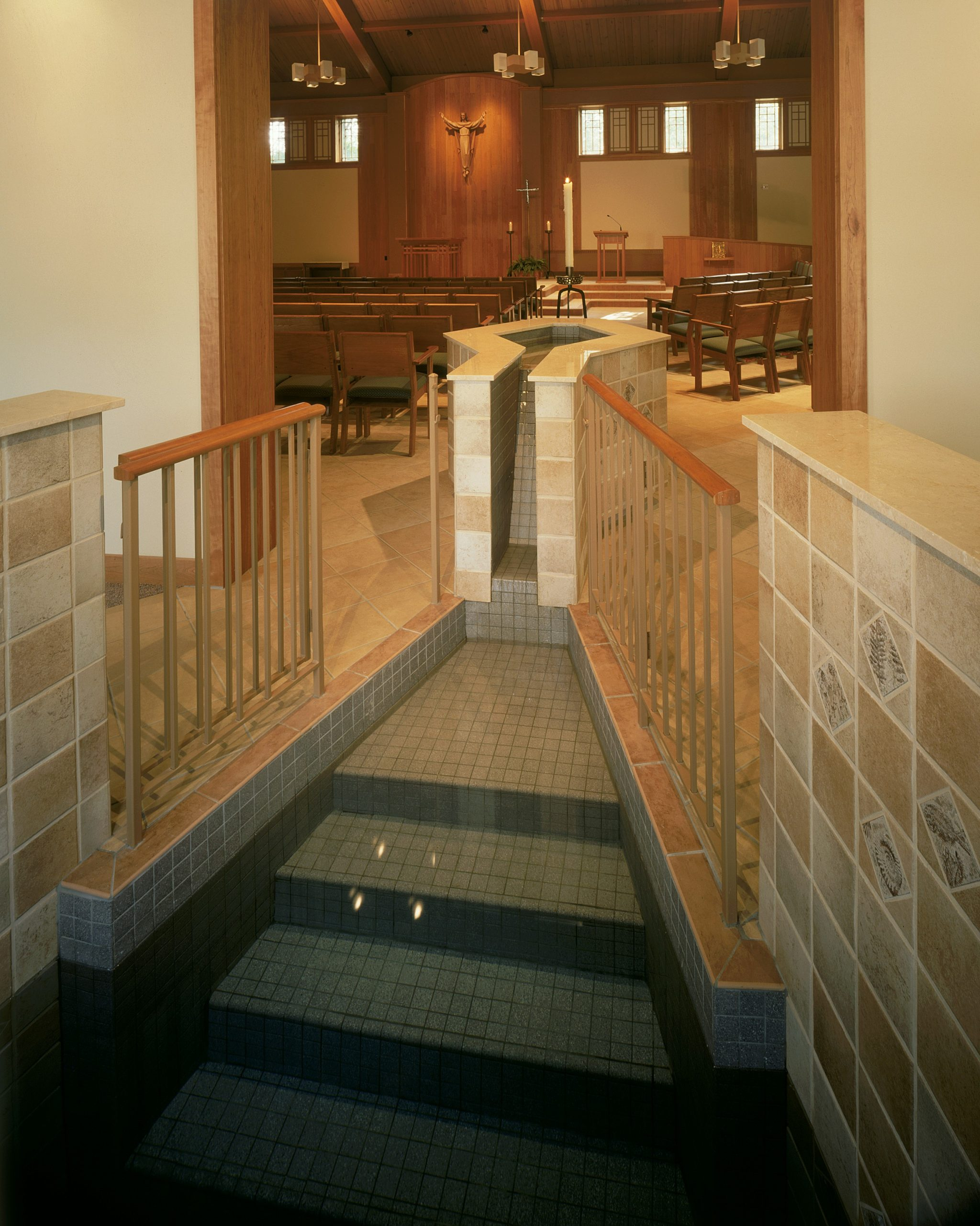 The new, step-down, tomb-shaped baptismal font with water flowing from the infant immersion font